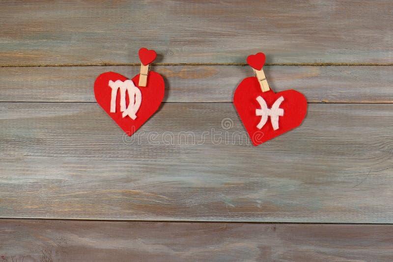 处女座和鱼 黄道十二宫和心脏 木背景 免版税图库摄影