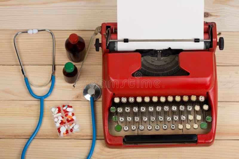 处方医学或医疗诊断-有听诊器的,药片,有白纸的打字机医生工作场所在木桌上 库存照片