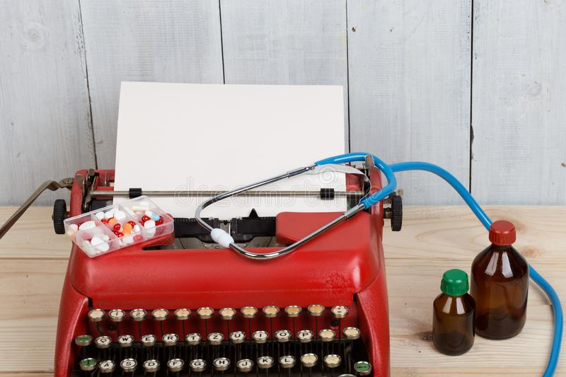 处方医学或医疗诊断-有听诊器的,药片,有白纸的打字机医生工作场所在木桌上 免版税图库摄影