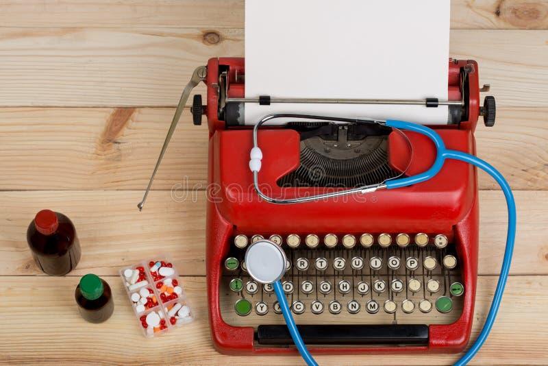 处方医学或医疗诊断-有听诊器的,药片,有白纸的打字机医生工作场所在木桌上 图库摄影