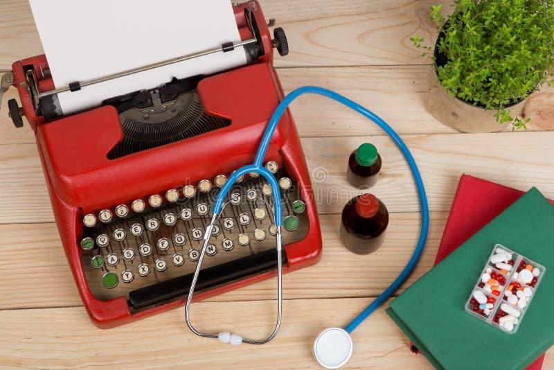 处方医学或医疗诊断-有听诊器的,药片,有白纸的打字机医生工作场所在木桌上 免版税库存照片