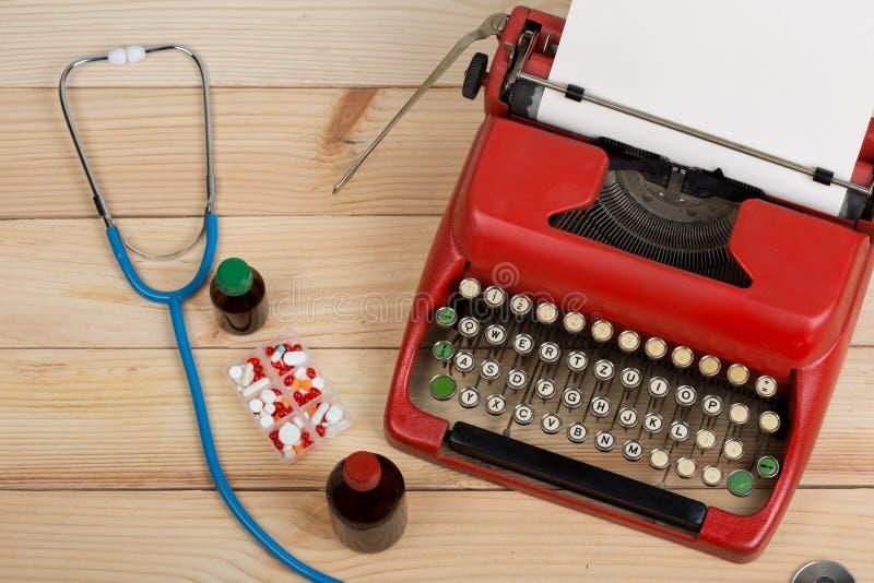 处方医学或医疗诊断-有听诊器的,药片,有白纸的打字机医生工作场所在木桌上 免版税库存图片