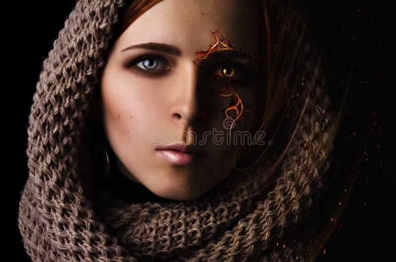 处理一个女孩的画象的有一个灼烧的样式的幻想在一条围巾的面孔在黑背景 免版税库存照片