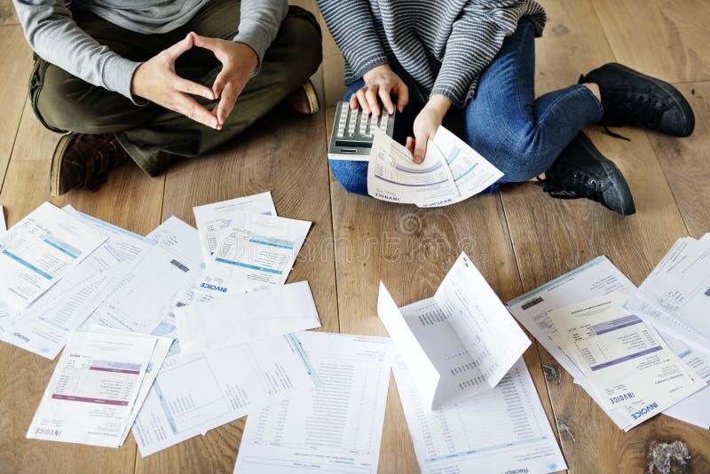 处理债务的夫妇通过计算 免版税图库摄影