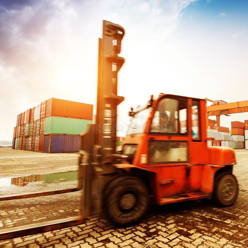 处理容器箱子的铲车在有美好的s的造船厂 图库摄影