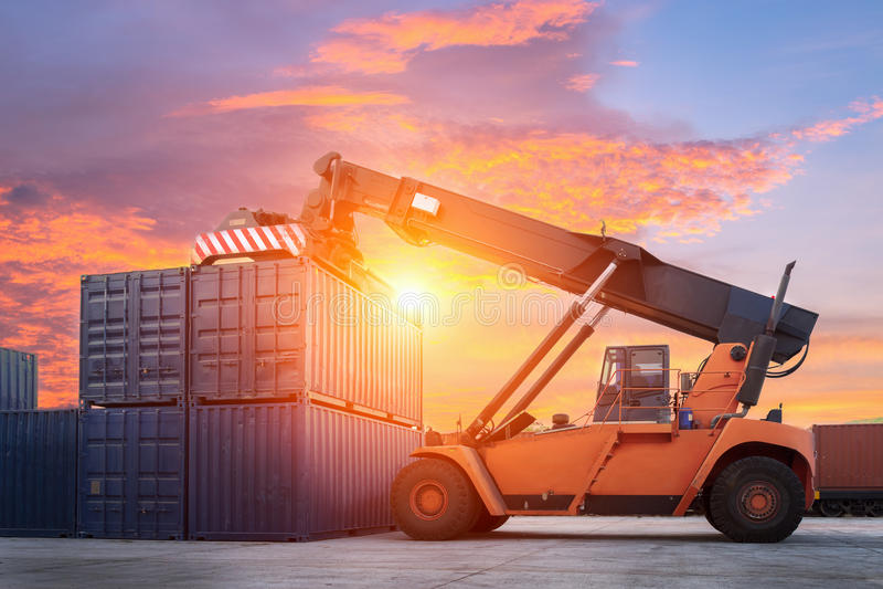 处理容器箱子的铲车装载对货车在进口,出口 库存照片
