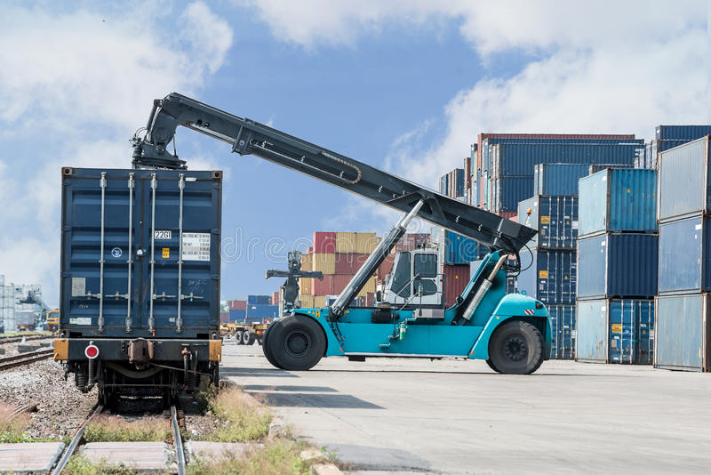 处理容器箱子的铲车装载对货车 免版税库存照片