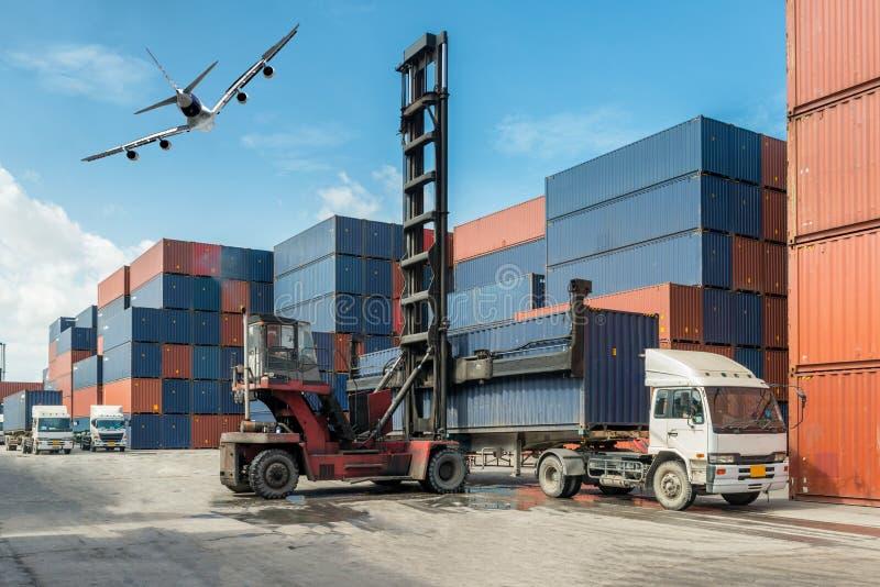 处理容器箱子装货的铲车在有卡车的船坞为 图库摄影