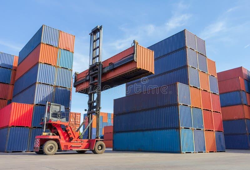 处理容器箱子装货的铲车对卡车在运输的庭院有货箱背景 免版税库存照片