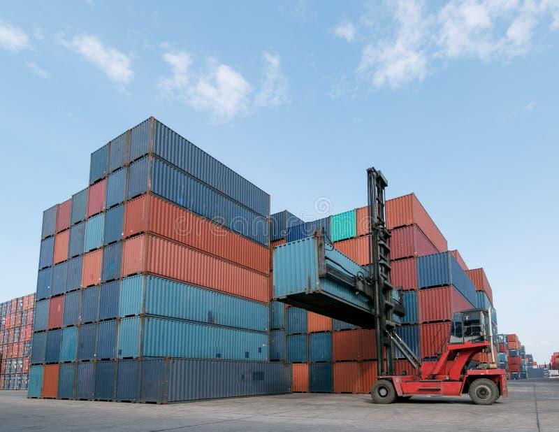 处理容器箱子装货的铲车对卡车在运输的庭院有货箱背景 库存照片