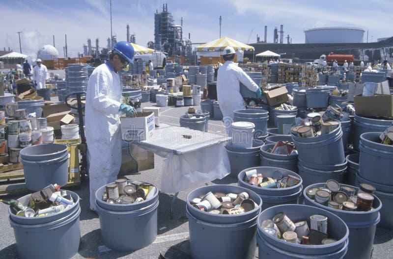 处理毒性家庭废物的工作者在世界地球日的废清洁站点在优尼科植物在威明顿,洛杉矶,加州 免版税库存图片