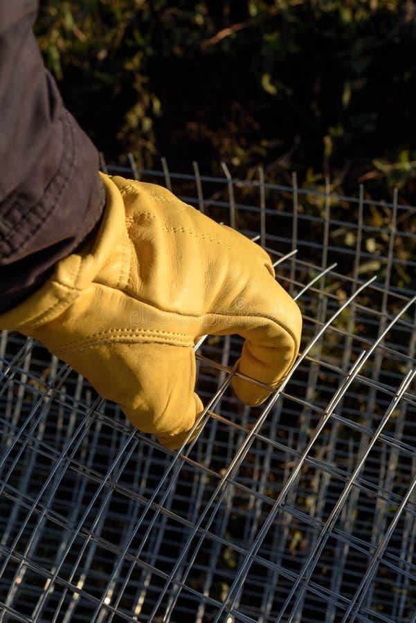 处理网状电线的男性黄色手套的手 库存照片