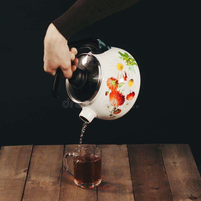 处理酿造茶,茶道,杯新近地酿造的红茶,温暖的柔光,更加黑暗的背景 免版税库存图片