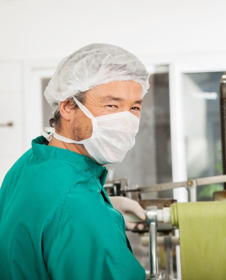 处理面团的防护工作服的愉快的厨师 免版税库存图片