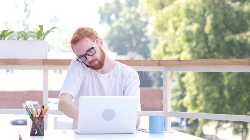处理顾客,电话谈话,坐在室外办公室,红色头发 免版税库存图片