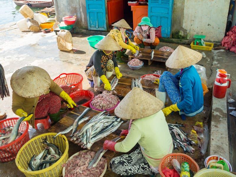 处理鱼肉的越南妇女在渔夫村庄在 免版税库存图片