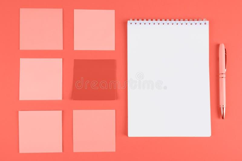 备忘录贴纸和笔记本在橙色背景 免版税库存照片