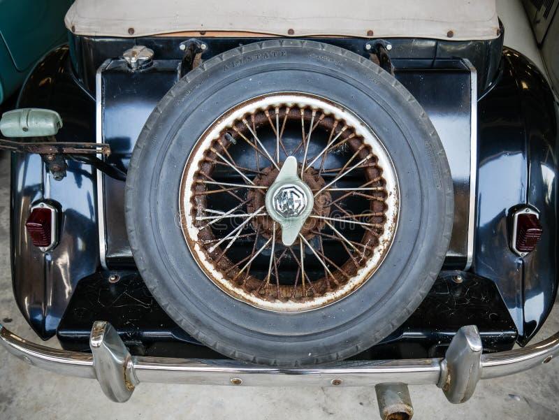 备用讲了在老神话英国汽车,减速火箭和葡萄酒背景后面树干的轮子  库存照片