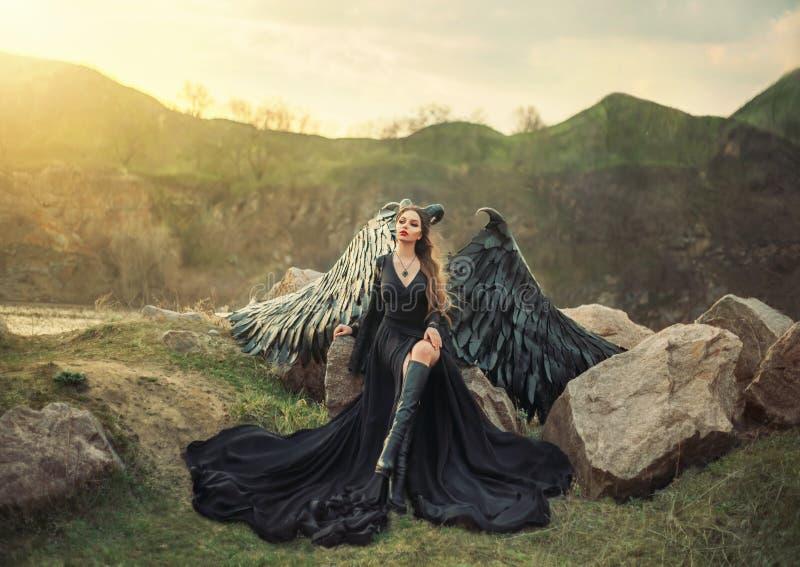 复兴的面貌古怪的人,夜观看的日出的女王/王后,长的轻的黑礼服的女孩有黑羽毛翼的坐岩石 库存照片