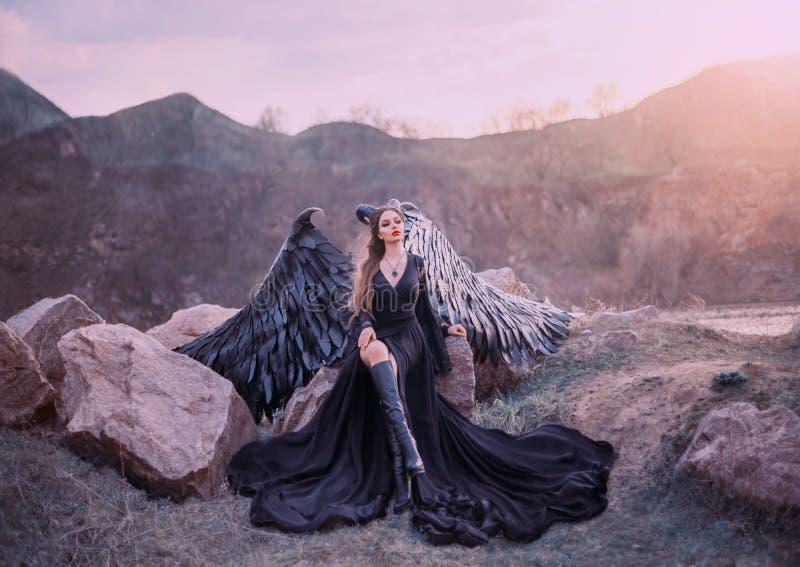 复兴的面貌古怪的人,夜观看的日出的女王/王后,长的轻的黑礼服的女孩有黑羽毛翼的坐岩石 免版税库存照片