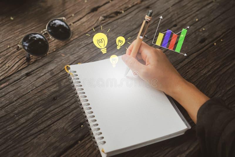 复制写下在有想法和图表象的白色笔记本的妇女手空间 免版税库存照片