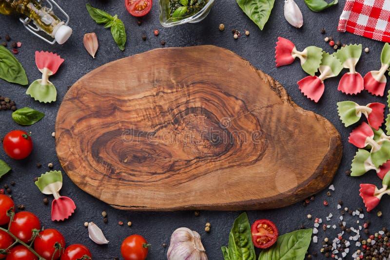 复制在木头裁减板的空间 Farfalle、西红柿、大蒜、蓬蒿、pesto、橄榄油、胡椒混合、盐和餐巾 图库摄影