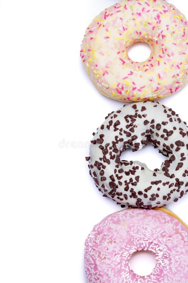 复制空间在白色backgr的被隔绝的五颜六色的甜点给上釉的油炸圈饼 库存图片