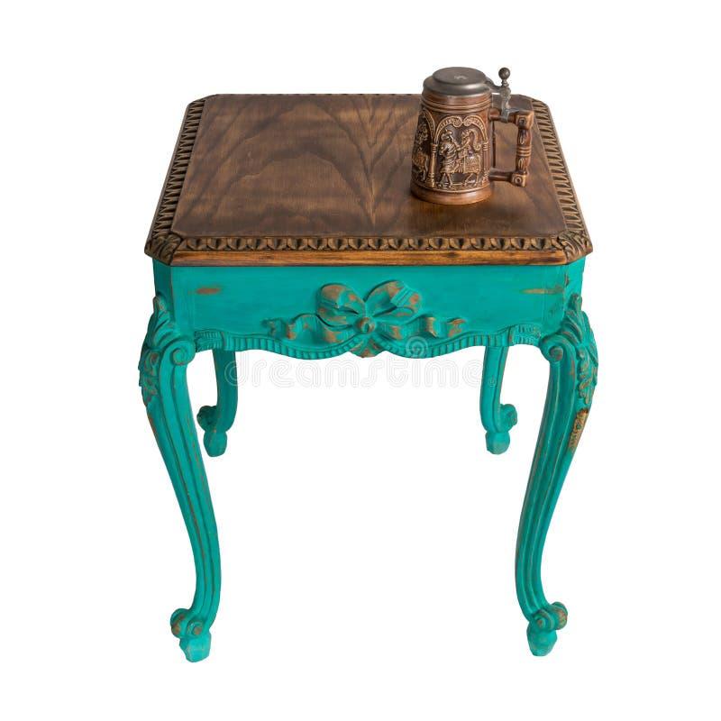 复古木复古桌,上面有绿色的双脚和茶壶,上面有修剪路径 库存图片