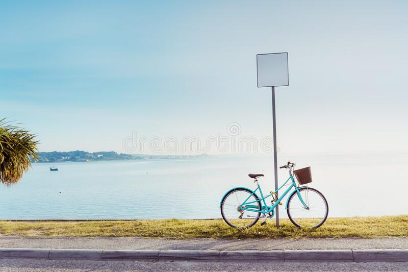 复古风格的明亮自行车停在海滨码头的空白路标旁 具有铺路行走的海景景观 库存图片