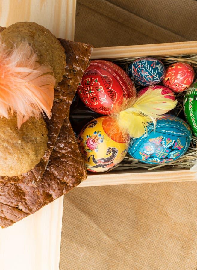 复活节上色了鸡蛋和羽毛在木背景 免版税库存照片