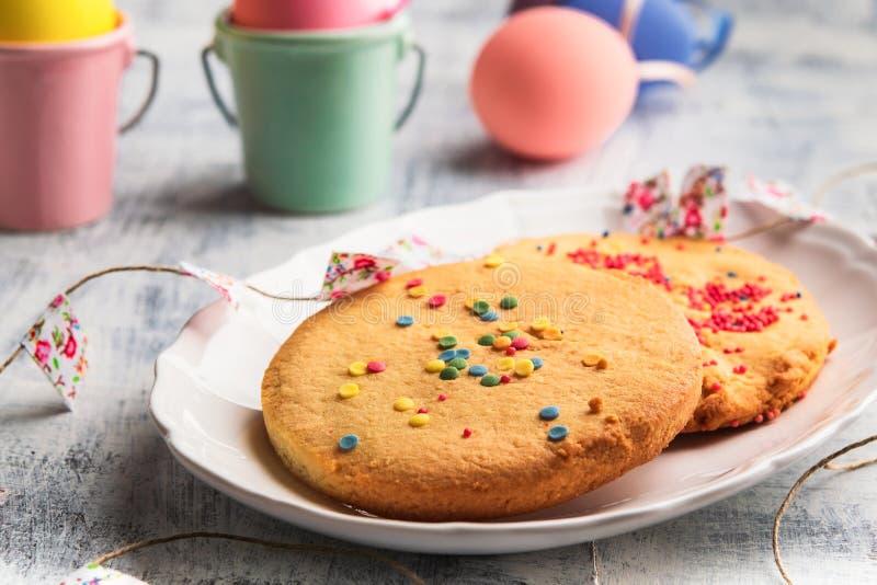 复活节与五颜六色的春天曲奇饼在一块白色板材洒 复活节愉快的概念 免版税库存照片