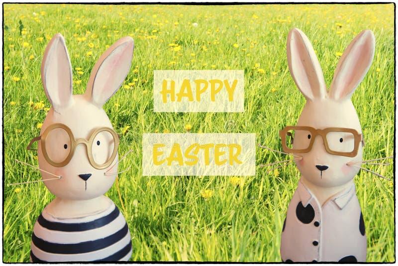 复活节与兔宝宝的贺卡在春天草甸 库存照片