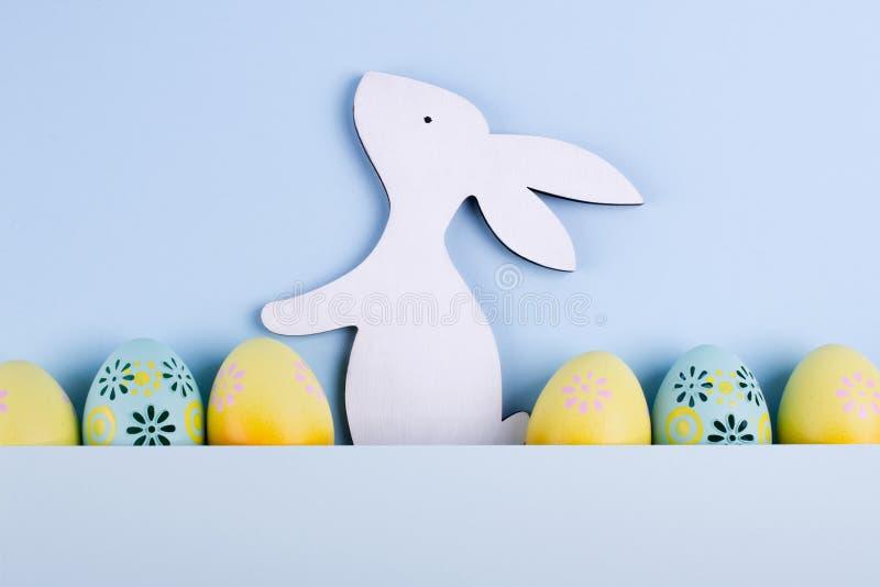复活节假日背景用鸡蛋 五颜六色的被绘的鸡鸡蛋连续plased的和装饰兔宝宝顶视图  免版税库存照片