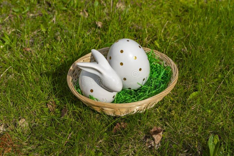 复活节兔子和复活节彩蛋由与金黄圆点的白色瓦器制成在篮子在草甸 库存照片