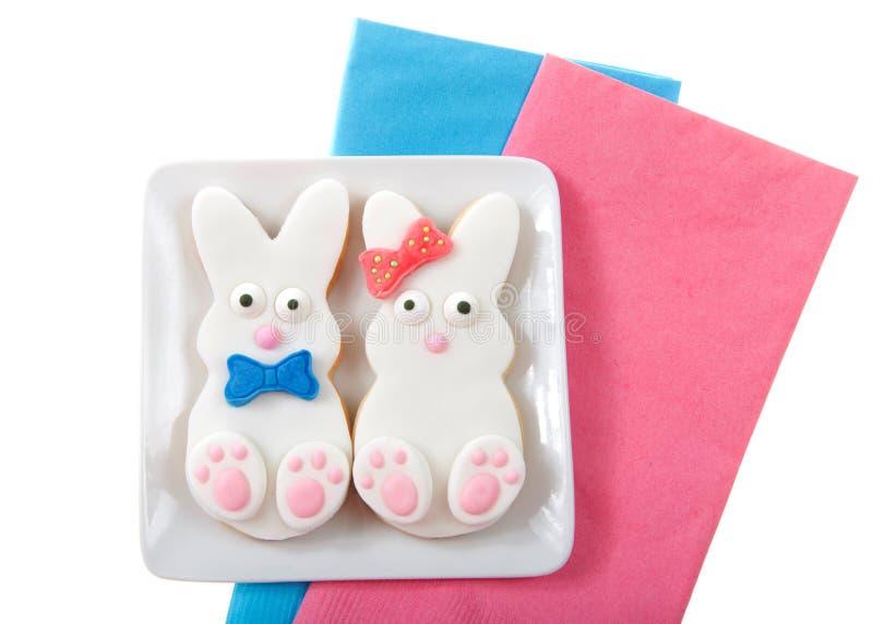 复活节兔子曲奇饼、男孩和女孩有弓的和蝶形领结在一块小方形的板材 免版税库存图片