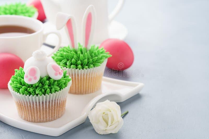 复活节兔子靶垛和耳朵杯形蛋糕用鸡蛋和茶 免版税库存图片