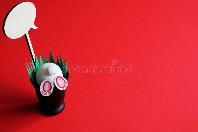 复活节兔子,在陶瓷花瓶的木轻便短大衣有绿草的由纸制成在明亮的不同的红色背景 最小的概念 免版税库存照片