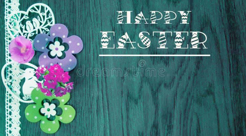 复活节卡片,在蓝色木头背景与花和装饰的 免版税库存照片