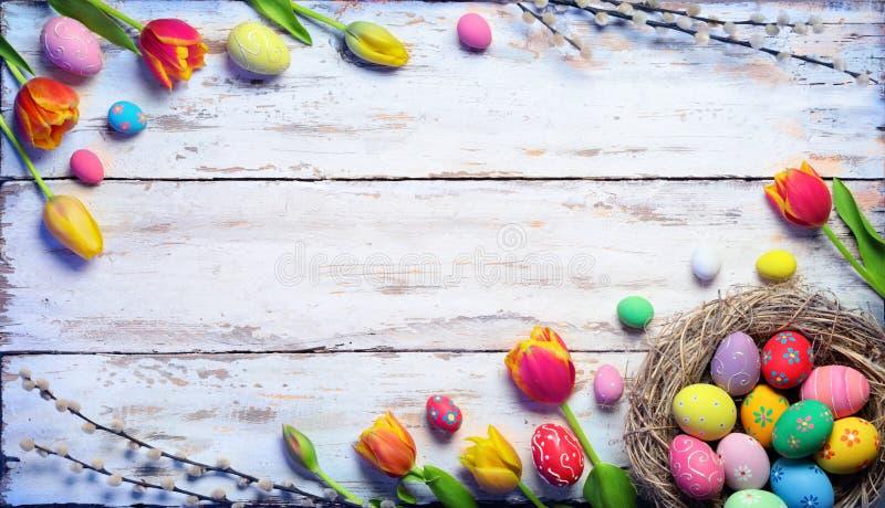 复活节卡片-在巢和郁金香的被绘的鸡蛋 免版税图库摄影