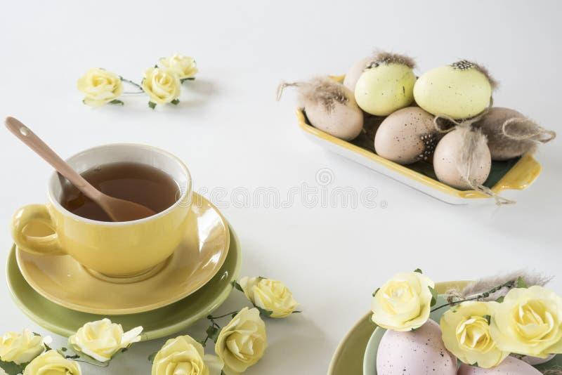 复活节在淡色的早晨场面,用茶和桃红色和黄色鸡蛋 免版税库存图片