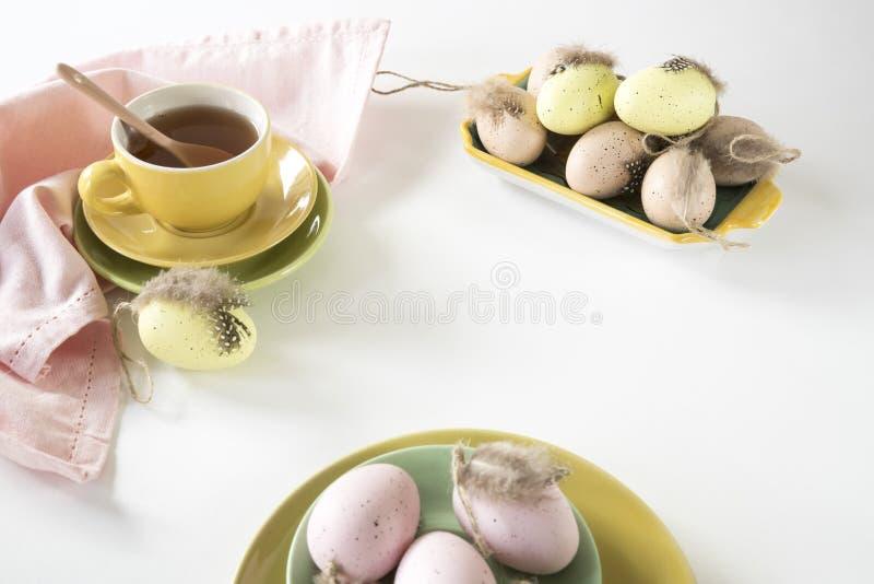 复活节在淡色的早晨场面,用茶和桃红色和黄色鸡蛋 免版税库存照片