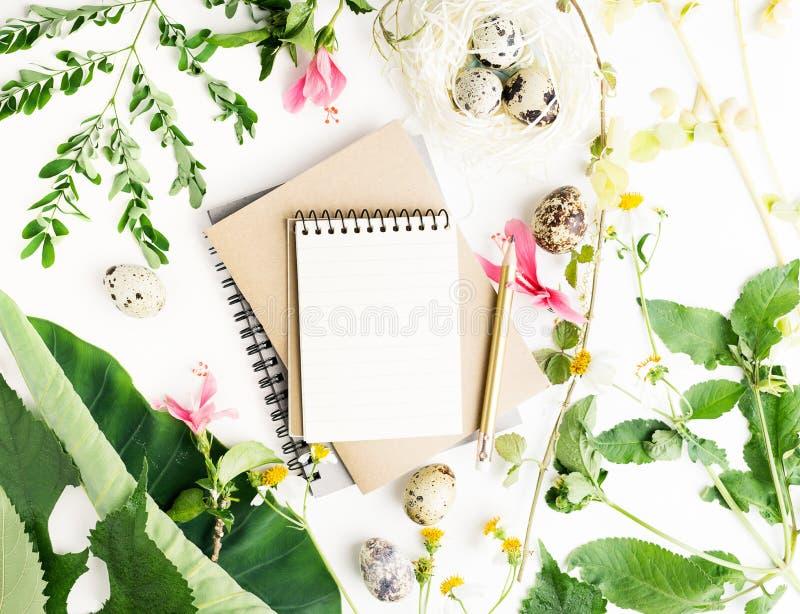 复活节大模型:顶视图舱内甲板放置笔记本和铅笔有春黄菊花、叶子和鹌鹑蛋的在纸巢 库存图片