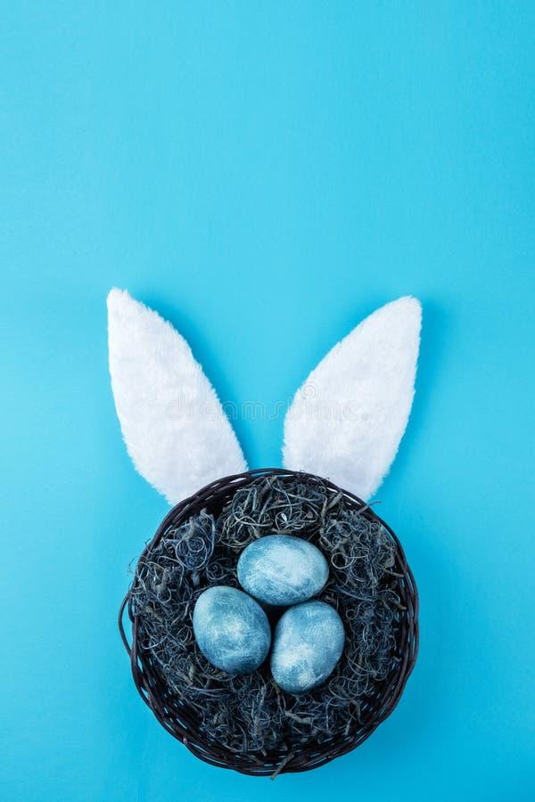 复活节巢用在颜色背景的蓝色鸡蛋 与装饰的欢乐花圈 免版税库存照片
