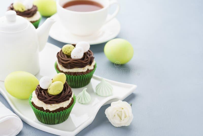 复活节巧克力杯形蛋糕装饰用巢和糖果鸡蛋 免版税图库摄影