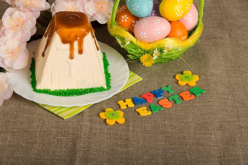 复活节彩蛋、乳酪蛋糕点心、题字复活节快乐和fl 免版税库存照片