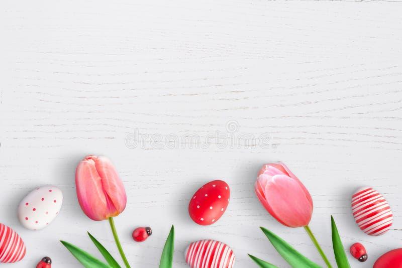 复活节彩蛋和春天郁金香开花白色木表面上 免版税库存照片