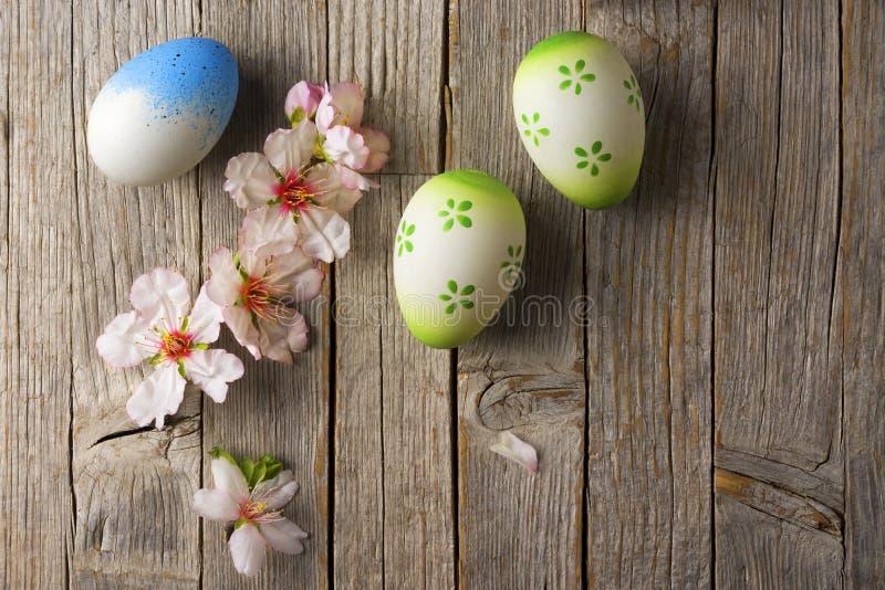复活节彩蛋和杏仁在老木桌上开花 库存照片