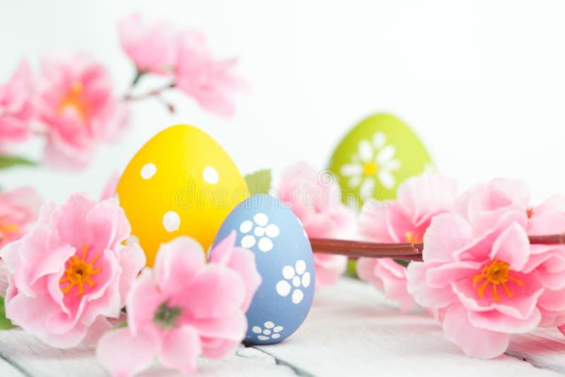 复活节彩蛋和桃红色花装饰在蓝色背景 免版税库存照片