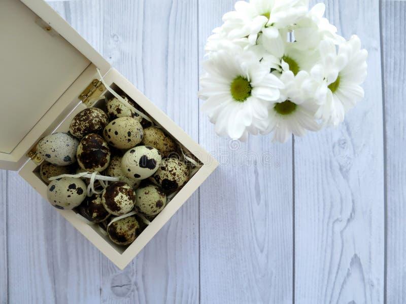 复活节彩蛋和白花在一张白色木桌上 免版税库存图片