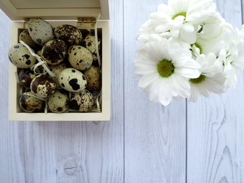 复活节彩蛋和白花在一张白色木桌上 图库摄影